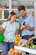 Couple Using Mobilephone While Shopping In Supermarket