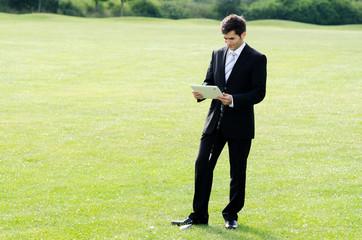 geschäftsmann mit tablet auf dem golfplatz