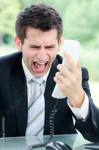 schreiender businessmann mit telefon