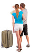 Back view journey of the young couple with suitcase looking at m