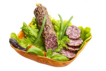 Ripe salami with salad, basil, onion and tomato