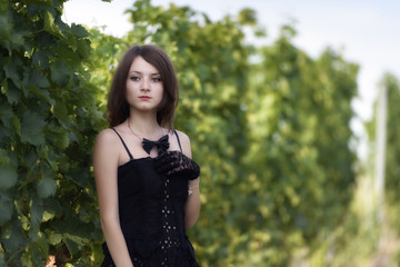 elegant young woman outdoor portrait lean on wall covered in vin