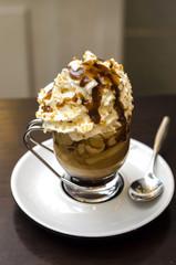 caffè con panna e caramello in tazza di vetro