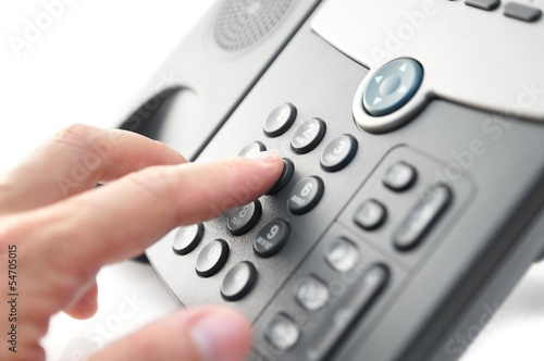 man's hand is dialing a phone number with picked up headset