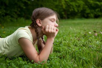 Mädchen auf einer Wiese beim Nachdenken