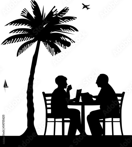 Elderly couple drinking coffee and reading a newspaper on beach