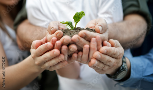 child with parents holding a new plant
