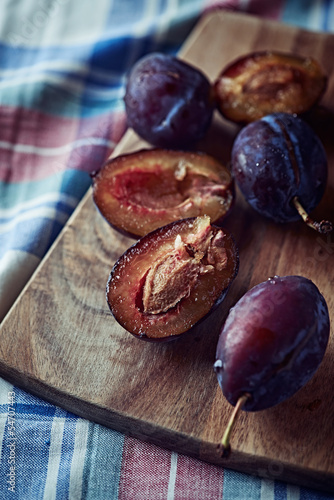 Whole and halved plums on a kitchen board
