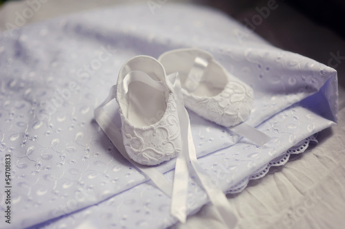 on a beautiful white embroidered bedspread baby slippers are