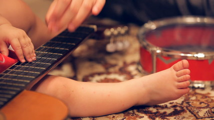 Little child learning to play guitar