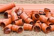 Leinwanddruck Bild - Orange Rohre aus Kunststoff liegen in trockenem Gras