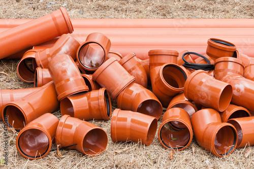 Leinwanddruck Bild Orange Rohre aus Kunststoff liegen in trockenem Gras