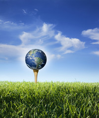 Earth as golf ball on tee with grass, blue sky