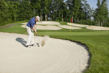 Golfer blasting out of bunker onto green