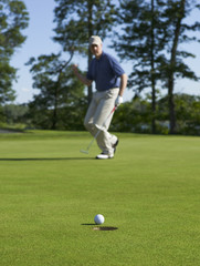 Golfer celebrates sinking putt on green