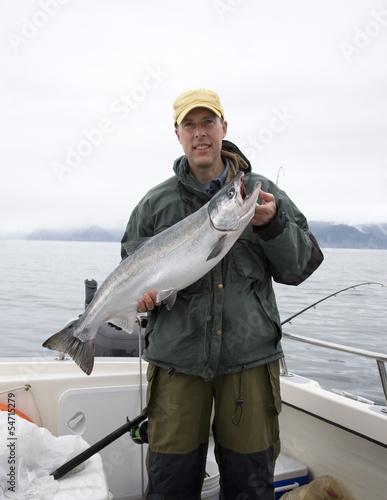 In de dag Vissen Happy fisherman in holds big silver salmon