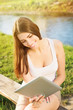 Cute student girl sitting by the river using tablet computer