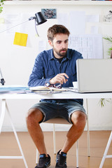 Young creative designer man working at office.