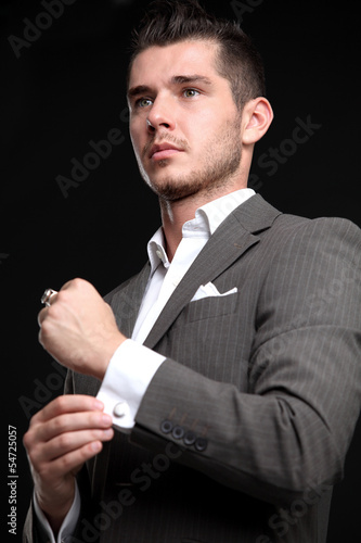 elegant fashion man looking at his cufflinks while fixing them