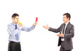 Guy showing a red card and blowing a whistle to a businessman