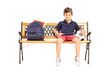 Schoolboy sitting on a wooden bench with school bag and football