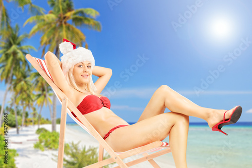 Young female in a santa costume sitting on a sun lounger on a be