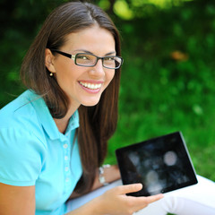 Young woman using tablet outdoor sitting on grass