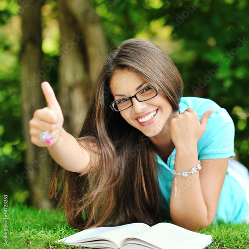 Portrait of young happy smiling cheerful woman in glasses lying
