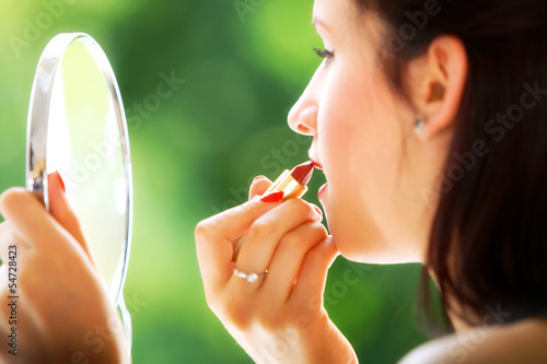 girl applying make up red lipstick in hand