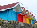 beach huts at the seaside with rock wall