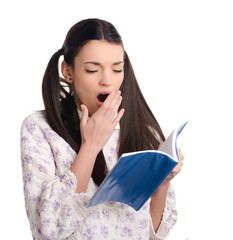 Beautiful girl in pajamas reading a book,bored,tired yawning.