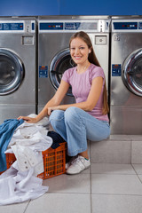 Woman With Laundry Basket Sitting In Front Of Washing Machine