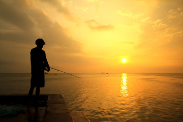 Fisherman fishes on the sea. Silhouette at sunrise