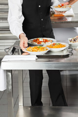Waiter Placing Pasta Dishes On Tray
