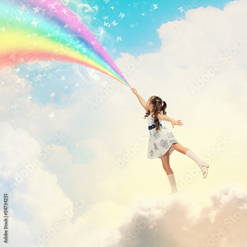 Little girl drawing rainbow