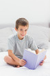 Smiling little boy sitting on bed reading book