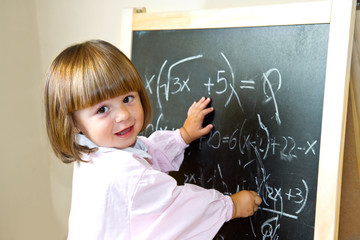 child draws with chalk on the blackboard