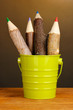 Colorful wooden pencils in green pail
