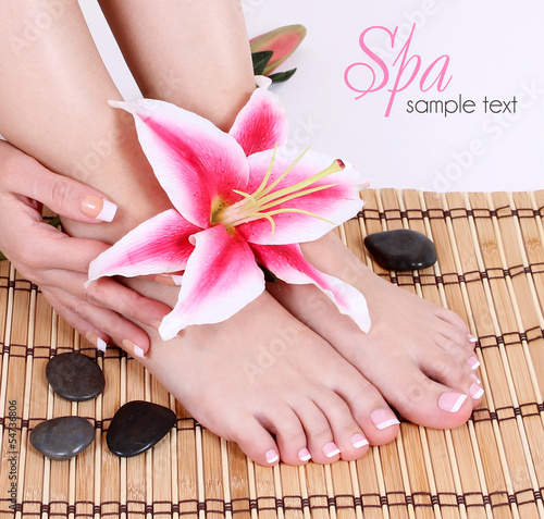 Manicured female bare feet with pink lily flower and spa stones