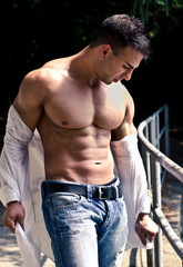 Attractive bodybuilder with open shirt showing torso muscles