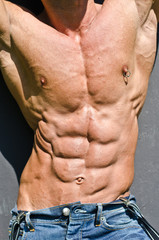 Bodybuilder torso with ripped abs and pecs with piercing