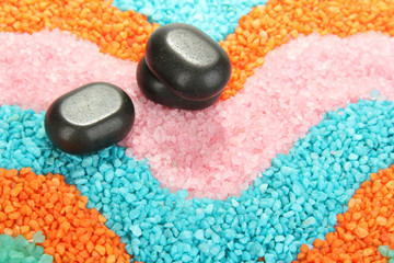 Black stones on colorful crystals of sea salt background