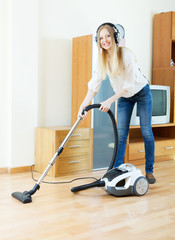 cheerful blonde woman in headphones  with vacuum cleaner