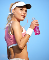 young attractive fitness woman drinking water, outdoors