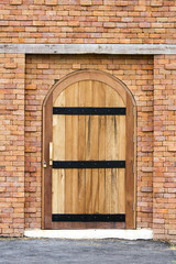 Wooden vintage closed door with brick wall to the house