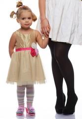 Little girl in golden dress holding mother's hand