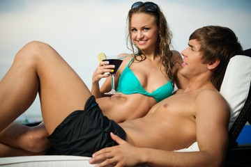 Sexy young couple relaxing with cocktail on a beach bed
