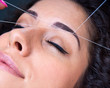 woman on facial hair removal threading procedure