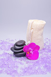 Massage stones, sponge and orchid on a white background