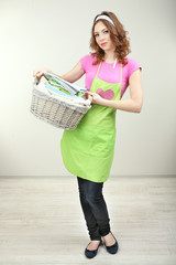 Housewife carrying laundry basket full of clothing in room